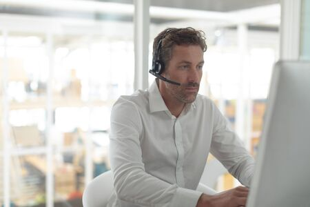 Front view of attentive Caucasian male customer service executive working at desk in a modern office Stok Fotoğraf