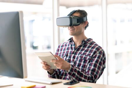 Side view of Caucasian male graphic designer using virtual reality headset while working on digital tablet at desk in office