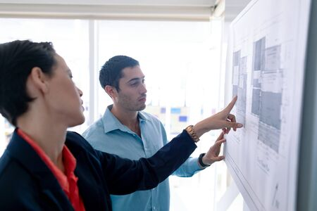 Side view of Caucasian architects discussing over blueprint on glass board in a modern office Stok Fotoğraf