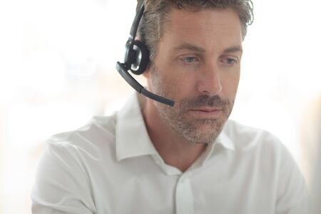 Front view of Caucasian male customer service executive talking on headset at desk in a modern office Stok Fotoğraf