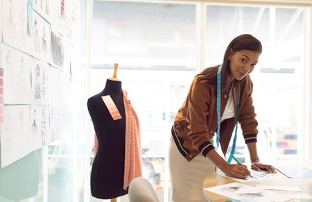 Side view of mixed race female fashion designer looking at camera while drawing sketch on table in a modern office Stock Photo - 124673203
