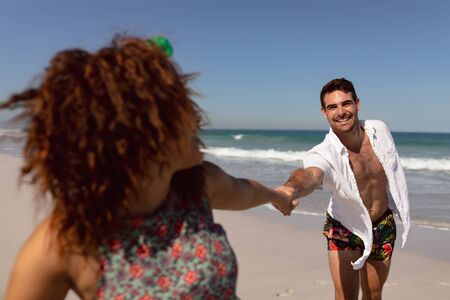 Front view of happy young Mixed-race couple holding hands on beach in the sunshine