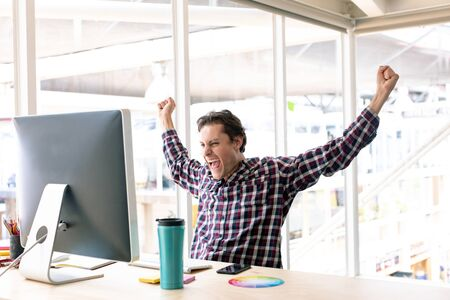 Side view of happy Caucasian male graphic designer celebrating success at desk in a modern office Stock Photo - 124673205