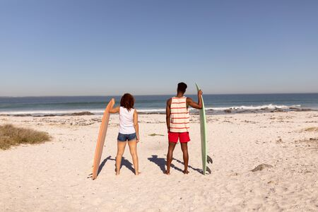 Rear view of couple standing with surfboard on beach in the sunshine Stok Fotoğraf