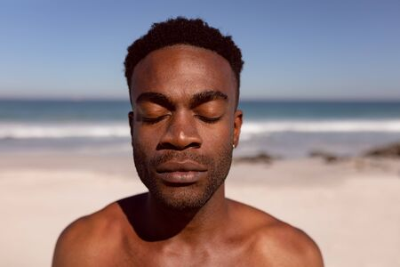 Front view of African-american man with eyes closed standing on beach in the sunshine