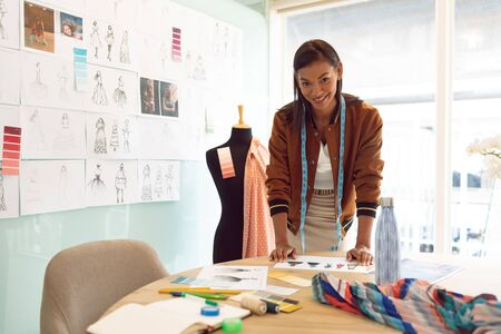 Front view of beautiful mixed race female fashion designer looking at camera while working on table in a modern office Stock Photo - 124673308