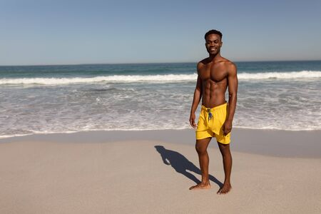 Front view of shirtless African-american happy man looking at camera on beach in the sunshine
