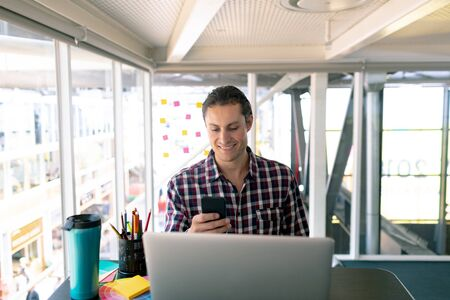 Front view of Caucasian male graphic designer using mobile phone while working on laptop at desk in office