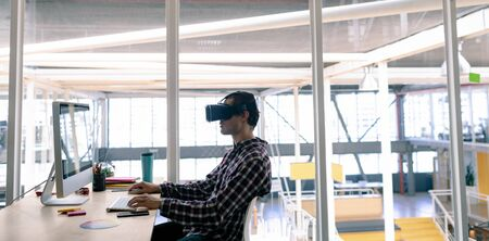 Side view of Caucasian male graphic designer using virtual reality headset while working on computer at desk in office Stock Photo - 124673324