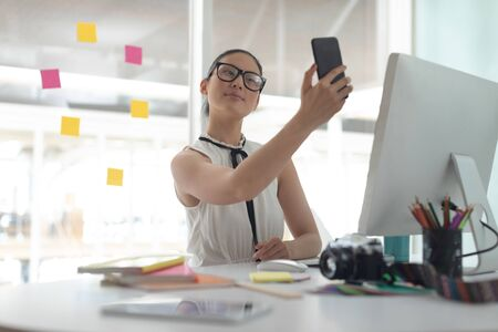 Front view of beautiful Asian female graphic designer taking selfie with mobile phone at desk in a modern office