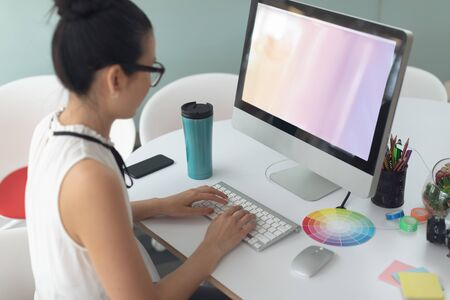 High angle view of Asian female graphic designer working on computer at desk in a modern office Stock Photo - 124673355
