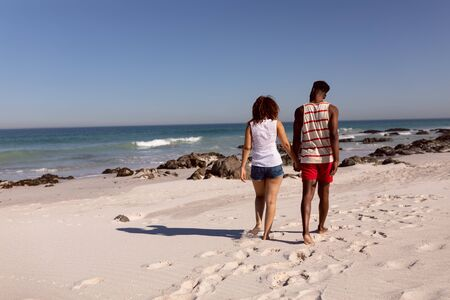 Rear view of Mixed-race couple holding hands and walking on beach in the sunshine