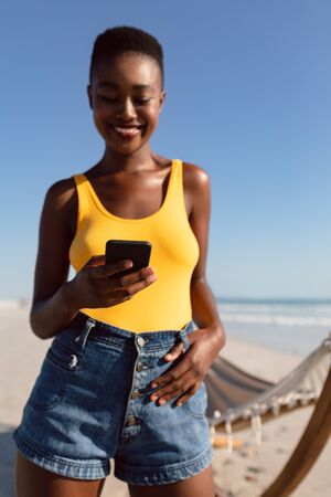 Front view of happy African-american woman using mobile phone with her thumbs in belt loops on the beach