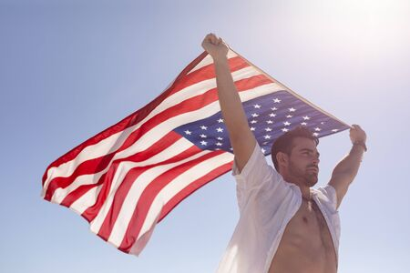 Low angle view of young Caucasian man waving american flag on beach in the sunshine