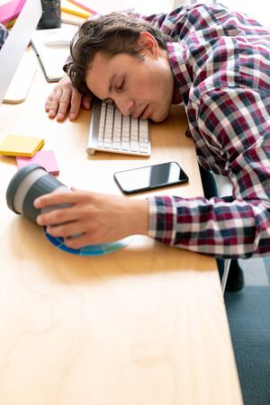 High view of tired Caucasian male graphic designer sleeping on desk in a modern office