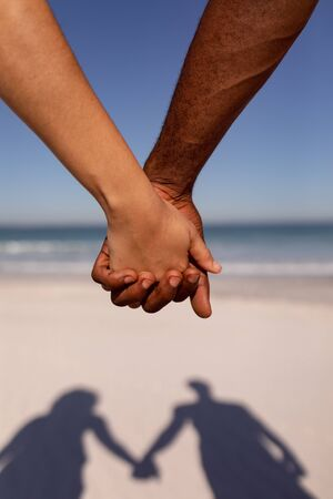 Close-up of Mixed-race couple holding hands on beach in the sunshine