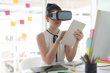 Front view of Asian female graphic designer using virtual reality headset and digital tablet at desk in a modern office