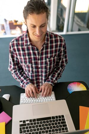 High view of Caucasian male graphic designer working on laptop at desk in office