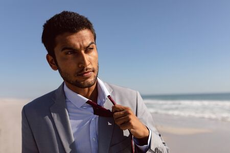 Portrait of thoughtful young Mixed-race Businessman removing his tie on the beach