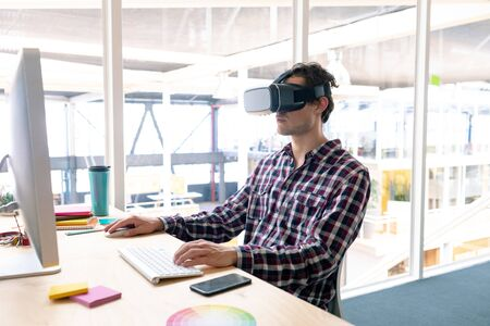 Side view of Caucasian male graphic designer using virtual reality headset while working on computer at desk in office Stock Photo