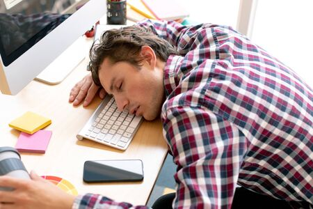 High view of tired Caucasian male graphic designer sleeping on desk in a modern office Stock Photo - 124673337