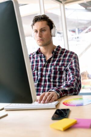 Front view of Caucasian male graphic designer listening music on headphone while working on computer at desk in a modern office