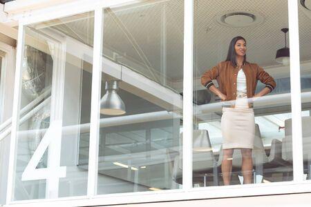 Vorderansicht einer glücklichen gemischten Geschäftsfrau mit den Händen auf den Hüften, die in einem modernen Büro in der Nähe des Fensters steht Standard-Bild