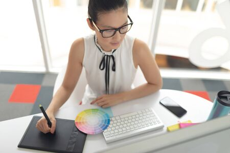 High angle view of Asian female graphic designer using graphic tablet at desk in a modern office Stock Photo - 124673347