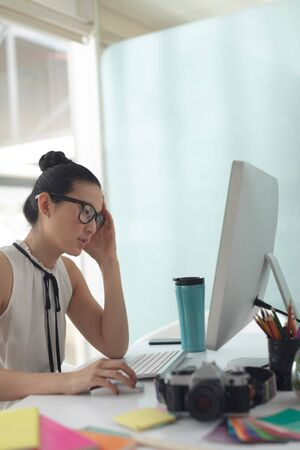 Side view of tensed Asian female graphic designer working on computer at desk in a modern office