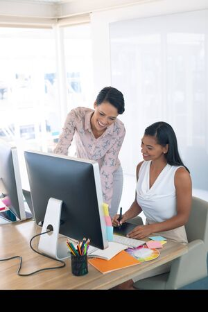 Front view of diverse female graphic designers discussing on computer at desk in a modern office Stock Photo - 124673281