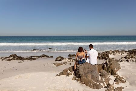 Rear view of young Mixed-race couple toasting beer bottle on beach in the sunshine