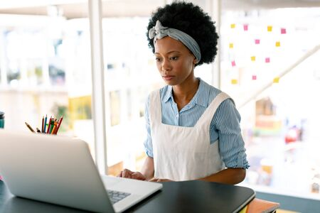 Front view of Caucasian female graphic designer working on laptop at desk in office