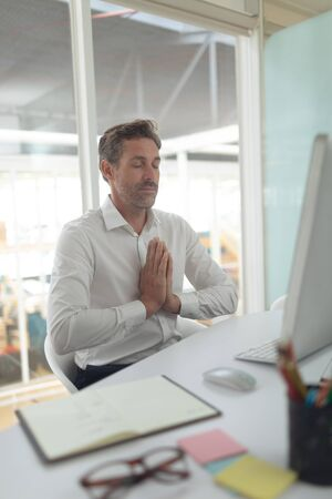 Front view of Caucasian business male executive doing yoga at desk in a modern office Stock Photo