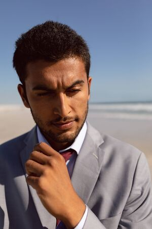 Portrait of thoughtful young Mixed-race Businessman standing on the beach