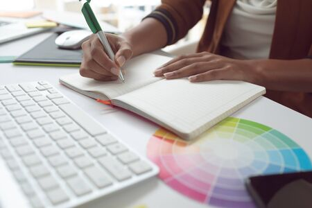 Mid section of Asian female graphic designer writing on diary at desk in a modern office Stock Photo - 124673294