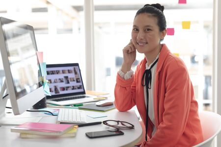Front view of beautiful Asian female graphic designer looking at camera on desk in a modern office Stock Photo
