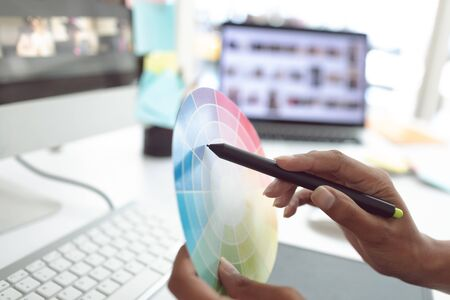 Close-up of Asian female graphic designer working with color swatch at desk in a modern office Stock Photo - 124673220