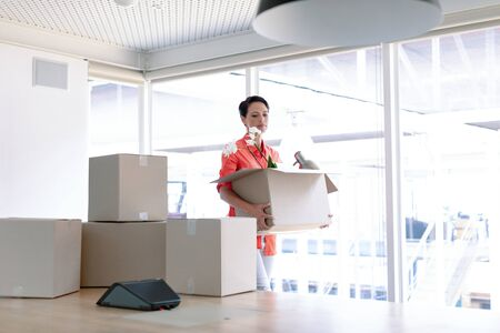 Side view of beautiful Caucasian businesswoman carrying cardboard boxes in new office Stok Fotoğraf