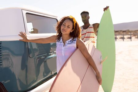 Front view of young Mixed-race couple with surfboard leaning on camper van at beach 版權商用圖片