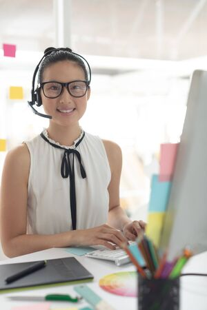 Front view of happy Asian female graphic designer in headset looking at camera while working at desk in a modern office