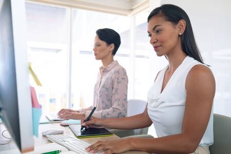 Side view of diverse female graphic designers working together at desk in a modern office