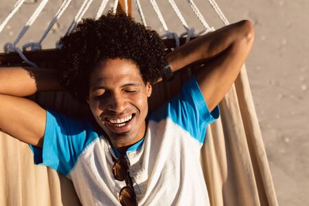 Front view of happy African-american man sleeping in a hammock on the beach Stok Fotoğraf