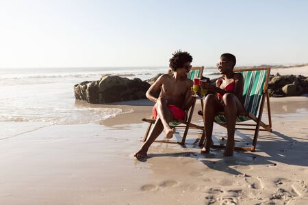 Front view of happy African-american couple toasting glasses of cocktail while relaxing in a beach chair on the beach Stok Fotoğraf
