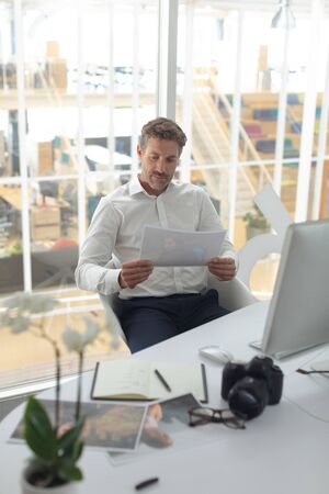 Front view of Caucasian male graphic designer looking at photograph on desk in a modern office