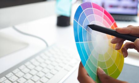 Close-up of Asian female graphic designer working with color swatch at desk in a modern office