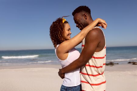 Front view of romantic Mixed-race couple embracing each other on beach in the sunshine 版權商用圖片
