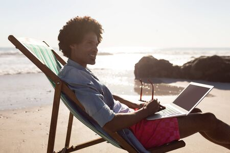 Side view of young African-american man using laptop while relaxing in a beach chair on the beach