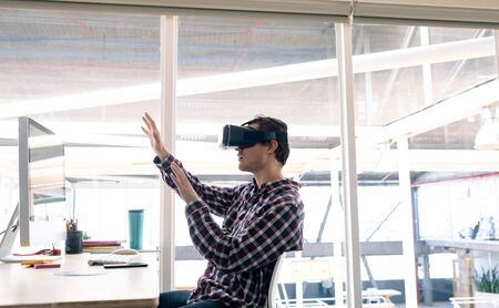 Side view of Caucasian male graphic designer using virtual reality headset at desk in office