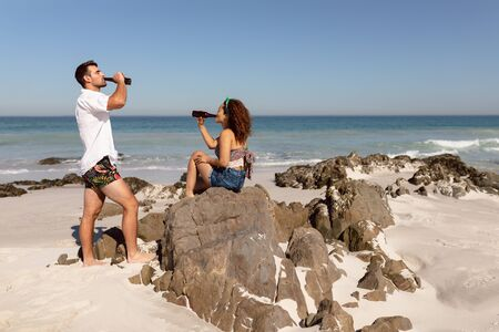 Side view of young Mixed-race couple drinking beer on beach in the sunshine