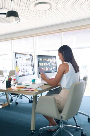 Side view of mixed race female graphic designer using digital tablet at desk in a modern office Stok Fotoğraf